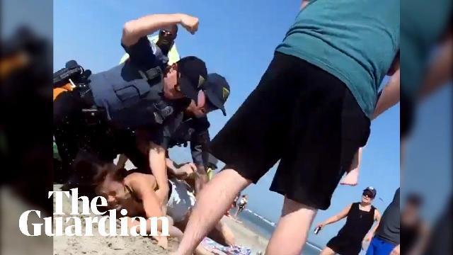 Cảnh sát Mỹ vật cô gái Emily Weinman xuống cát và đấm 2 lần vào đầu