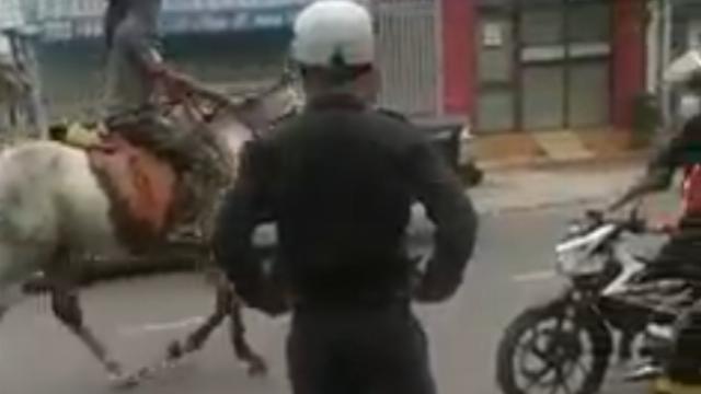 Hai thầy trò ung dung cõng nhau đi qua hàng loạt các chiến sĩ cảnh sát, công an