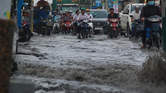 Người Sài Gòn vật vã dắt xe chết máy qua đường ngập