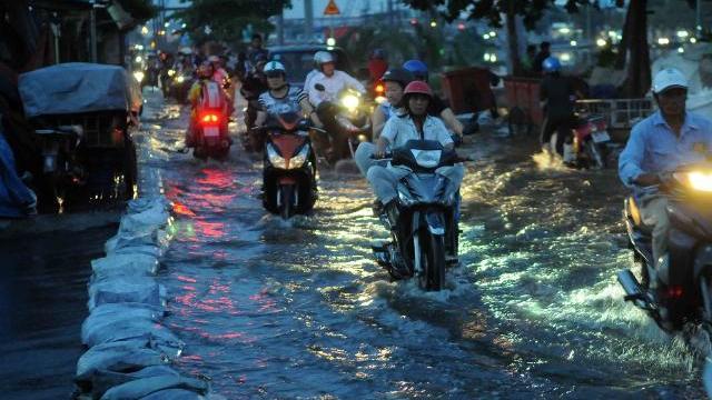 Triều cường đạt đỉnh, người đi xe máy ngã nhào trong biển nước