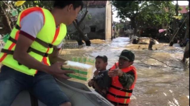 Cậu bé bơi trong nước lũ ra nhận đồ cứu trợ khiến dân mạng xúc động